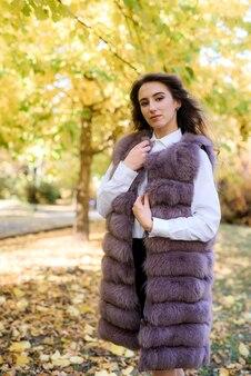 Vrouw dragen van modieuze bontjas wandelen in herfst park.