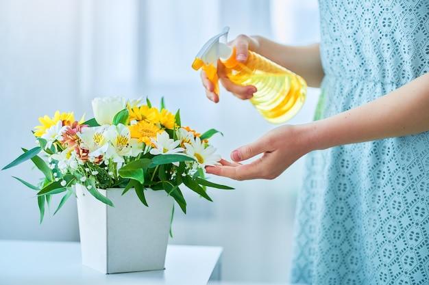 Vrouw drenken kleurrijke heldere verse bloemen op decoratieve hoedendoos met sproeiflacon op lentedag
