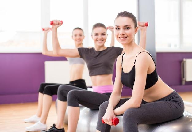 Vrouw drie met oefeningsballen en domoren in gymnastiek.