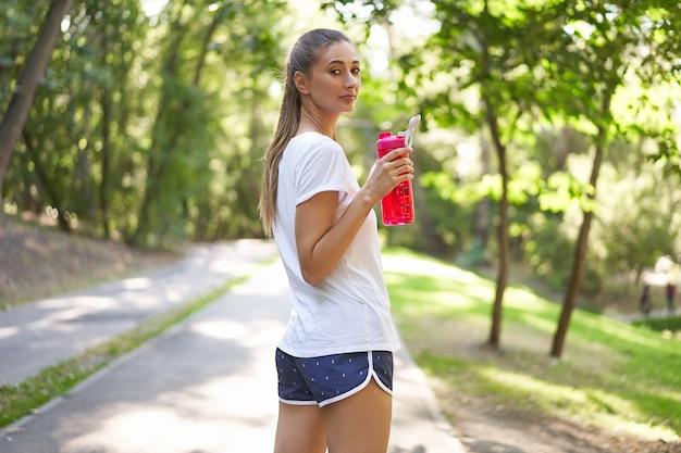 Vrouw drink rode waterfles na ochtendtraining.