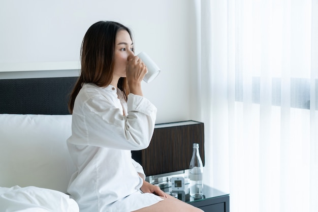 Vrouw drinken uit een theekopje zittend in bed