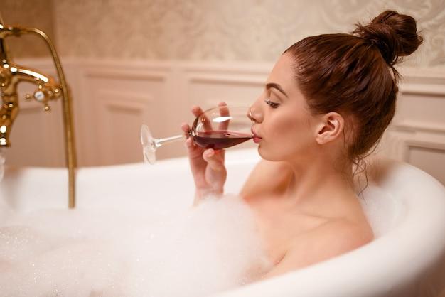 Vrouw drinken van rode wijn in de badkuip