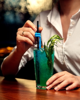 Vrouw drinkt blauwe cocktail met dragon