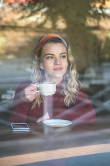 Vrouw drinkt cappuccino in een koffieshop zittend aan een tafel bij het raam.