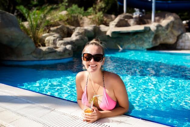 Vrouw drinkt cocktail en baadt in het zwembad