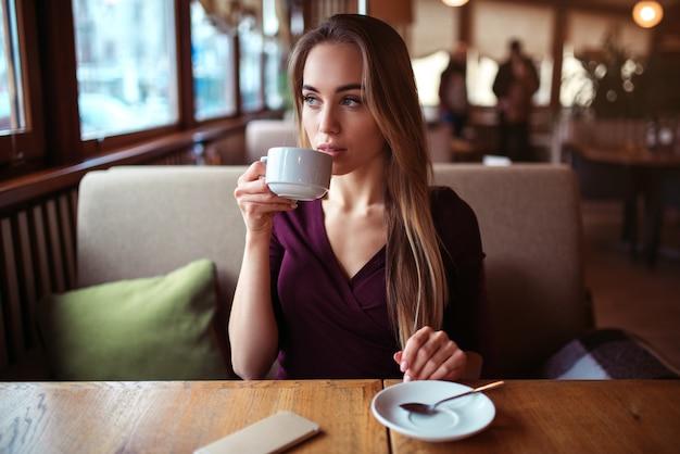 Vrouw drinkt drank in café.