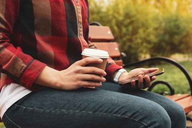 Vrouw drinkt koffie en gebruikt smartphone in park. lunchpauze
