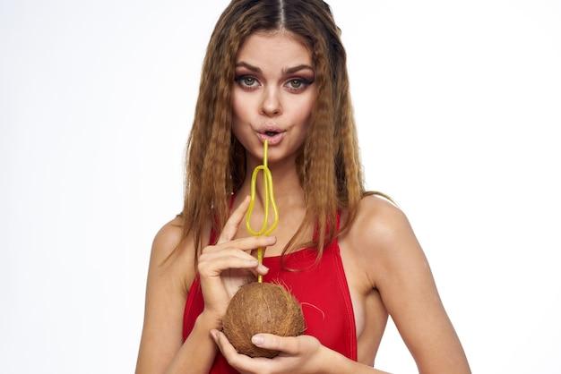 Vrouw drinkt kokosnoot cocktail met een rietje levensstijl rood t-shirt licht