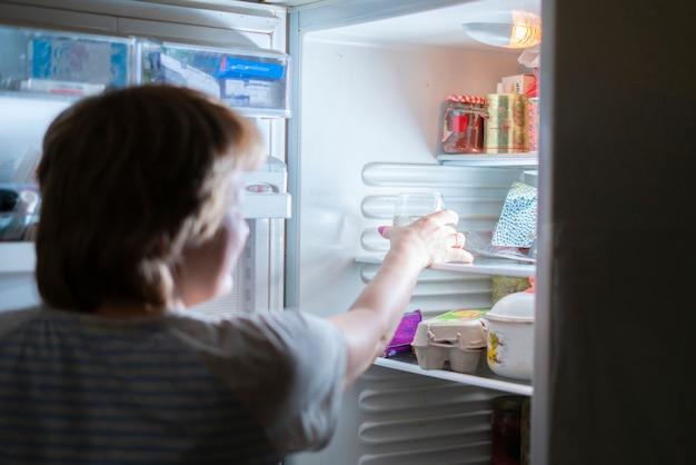 Vrouw drinkt om middernacht water uit de koelkast