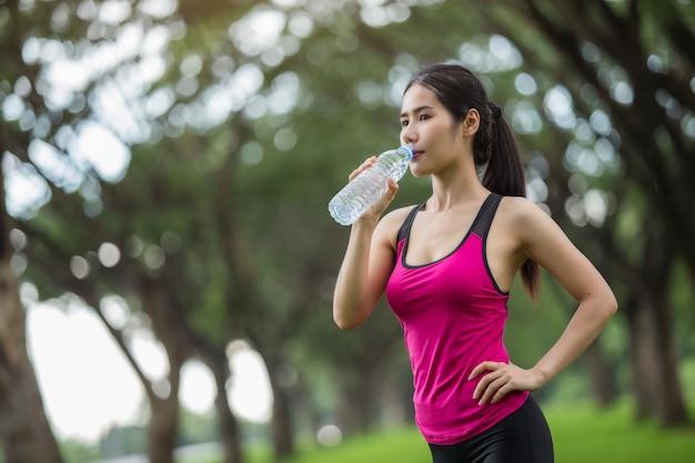Vrouw drinkt water uit de oefening.