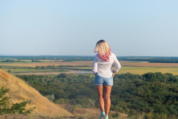Vrouw droeg een wit overhemd en een blauwe korte broek met lang blond roze haar dat op de berg stond