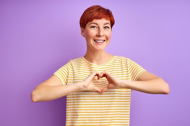 Vrouw drukt liefde uit met vorm van hart gemaakt van handen, glimlach