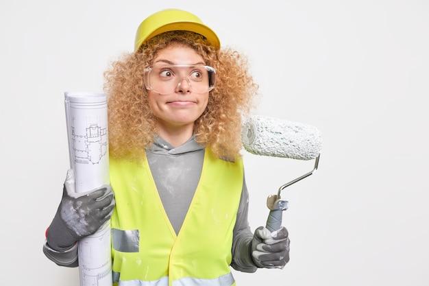 Vrouw drukt lippen gefocust in de verte draagt beschermende helm uniform en veiligheidsbril als professionele decorateur houdt rol blauwdruk poses binnen. reparatieservice aan huis