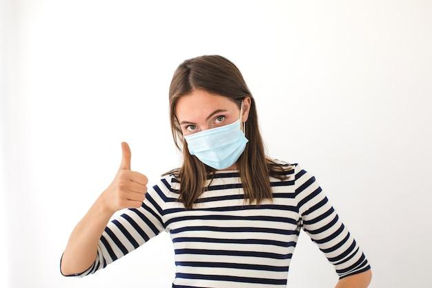 Vrouw duim opdagen. mooie blanke jonge vrouw met wegwerp gezichtsmasker. bescherming tegen virussen en infectie. studio portret, concept met witte achtergrond