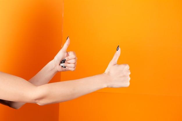 Vrouw duim opdagen op oranje background