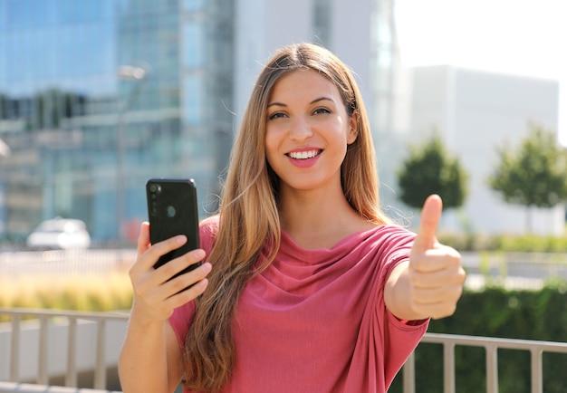 Vrouw duimen omhoog met smartphone in haar hand