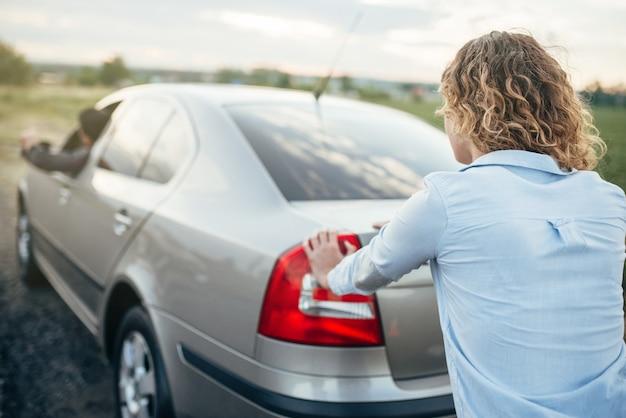 Vrouw duwt een kapotte auto, achteraanzicht, mannelijke bestuurder. voertuig met problemen langs de weg