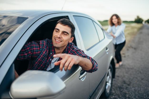 Vrouw duwt een kapotte auto op de weg, lachende man bestuurder. voertuig met problemen