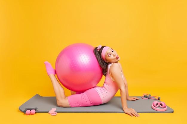 Vrouw dwaast rond terwijl het doen van pilates-oefeningen grimastreinen maakt met fitball-houdingen op mat omringd door sportuitrusting blijft fit. actieve levensstijl en trainingsconcept