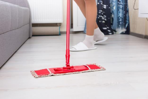 Vrouw dweilt de tegelvloer in een woonkamer met een kleurrijke rode dweil, lage hoek van haar benen en het hoofd van de dweil