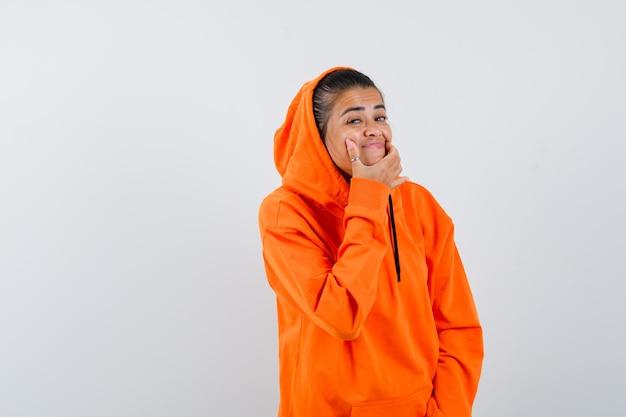 Vrouw dwingt een glimlach op het gezicht in oranje hoodie en ziet er raar uit