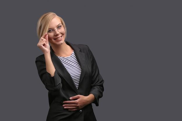 Vrouw, een leraar in een jas en een bril op een grijze achtergrond, drukt emoties uit. copyspace.