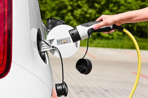 Vrouw een oplader loskoppelen van een elektrische auto-aansluiting. milieuvriendelijk voertuig zonder uitstoot