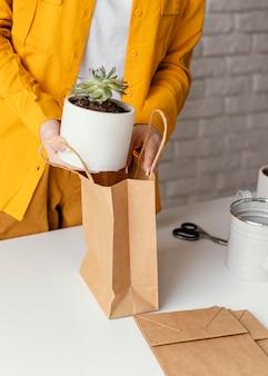 Vrouw een plant aanbrengend een papieren zak