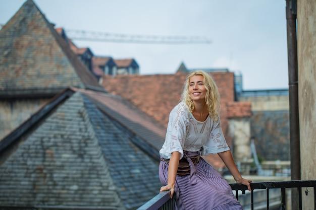 Vrouw een volwassen jonge mooie en gelukkige blonde op een balkon tegen de achtergrond van de oude daken van een mooie europese stad