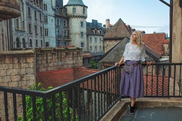 Vrouw een volwassen jonge mooie en gelukkige blonde op een balkon tegen de achtergrond van een oude mooie europese stad