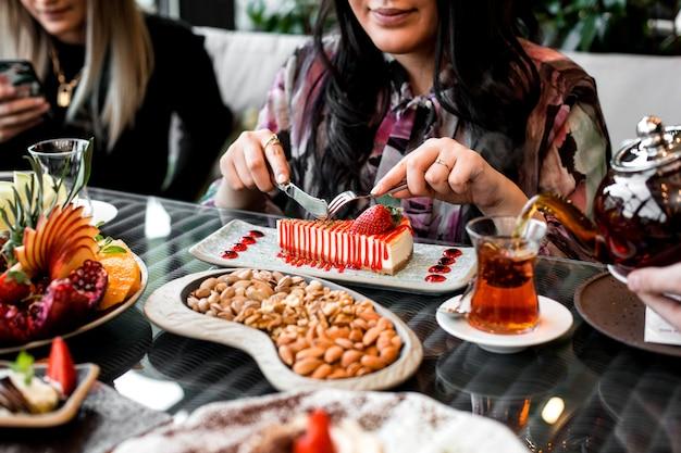 Vrouw eet aardbeien cheesecake geserveerd met thee