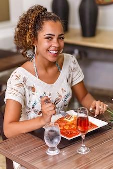 Vrouw eet een heerlijk gerecht van vlees en noedels parmigiana.