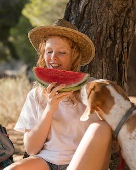 Vrouw eet een plakje watermeloen en hond is op zoek