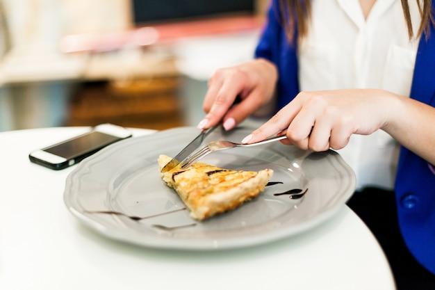 Vrouw eet een taart in het cafe