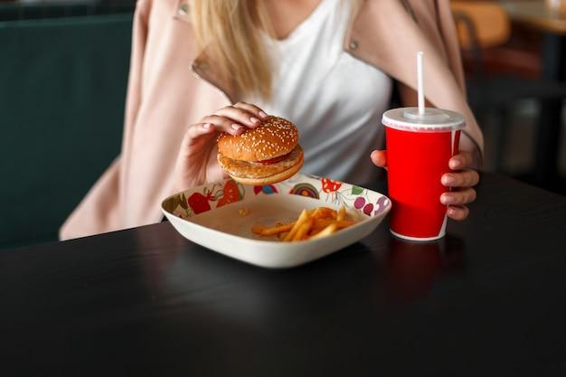 Vrouw eet fastfood. hamburger met frietjes en een rode kop met een drankje op de houten tafel
