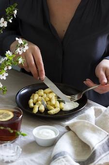 Vrouw eet gestremde gnocchi. ontbijttafel met gnocchi en thee.