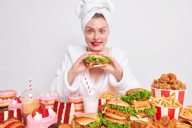 Vrouw eet gretig hamburger houdt van cheat meal en ongezond junkfood heeft een eetgewoonte draagt badjas en handdoek op het hoofd omringd door verschillende smakelijke traktaties op wit