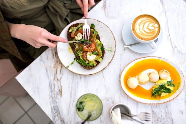 Vrouw eet haar smakelijke brunch op hipster café, bovenaanzicht van marmeren tafel, zalm avocado toast, koffie en zoete smakelijke cheesecakes, genietend van haar ontbijt.
