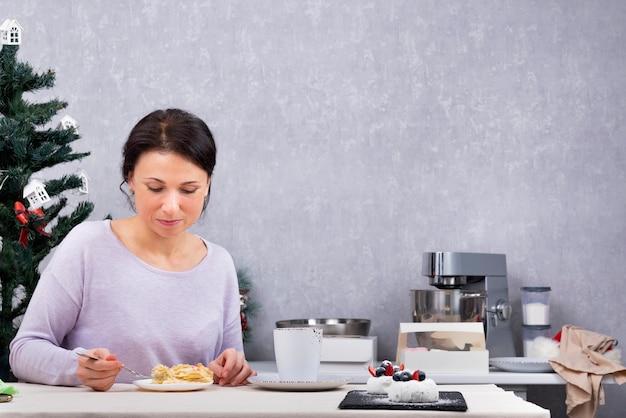 Vrouw eet in haar keuken. ontbijt met dessert. vakantie.