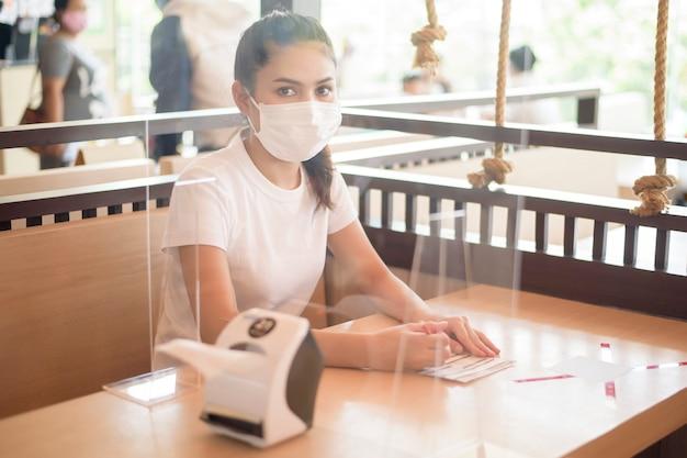 Vrouw eet in restaurant met sociaal afstandsprotocol terwijl ze stad afsluit vanwege een pandemie van het coronavirus