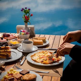 Vrouw eet omelet met groenten, pannenkoeken eten met chocolade, cake op een houten tafel