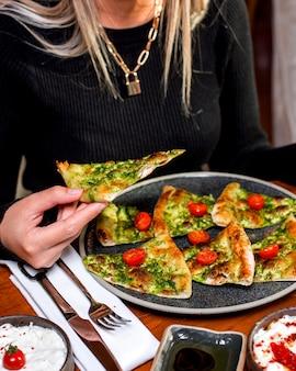 Vrouw eet pizza met groenen geserveerd met kerstomaatjes