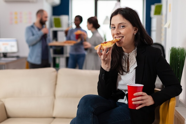 Vrouw eet pizza op after work party met vrienden