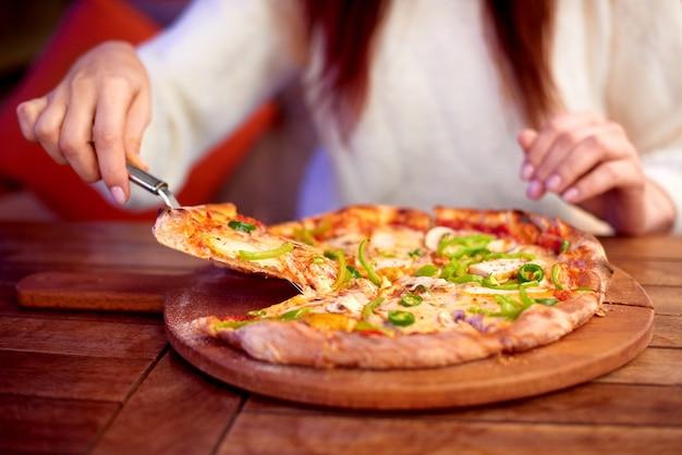 Vrouw eet pizza thuis vrouw hand neemt plak van gesneden pizza met mozzarella kaas tomaten