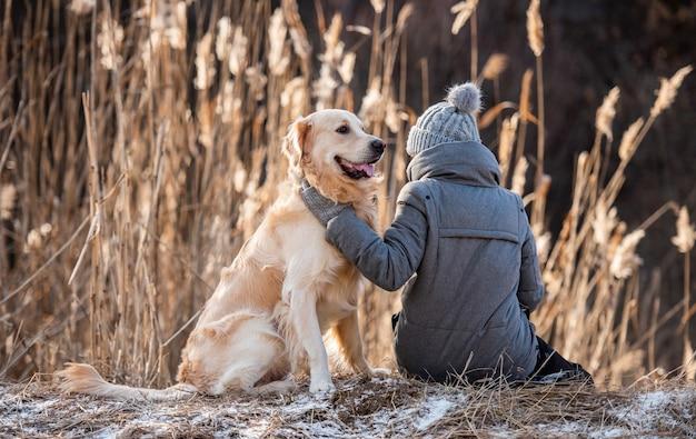 Vrouw eigenaar zittend op de grond met golden retriever hond en hem aaien tijdens vroege lente wandeling...
