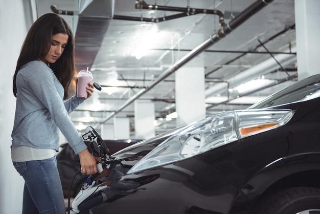 Vrouw elektrische auto opladen bij laadstation voor elektrische voertuigen