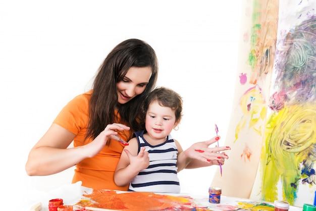 Vrouw en baby's tekenen zittend aan tafel