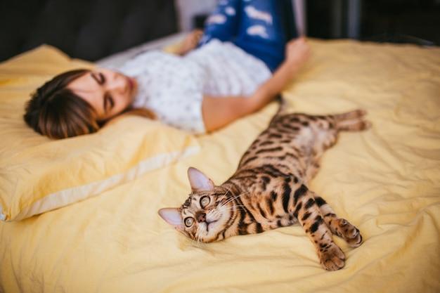 Vrouw en bengaalse kat liggen op het bed