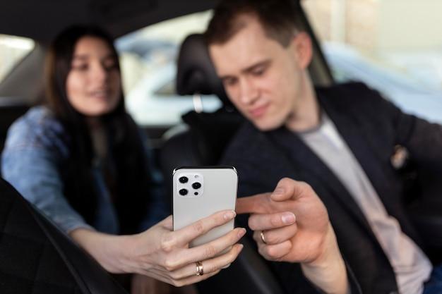 Vrouw en chauffeur kijken naar telefoon