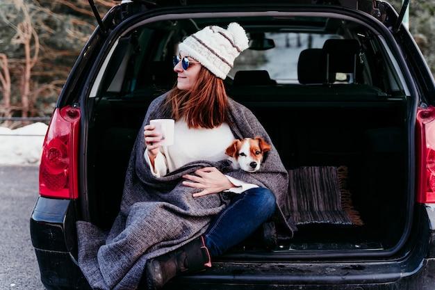 Vrouw en de leuke hond die van hefboomrussell in openlucht bij de berg in de auto genieten van. reizen concept. winter seizoen